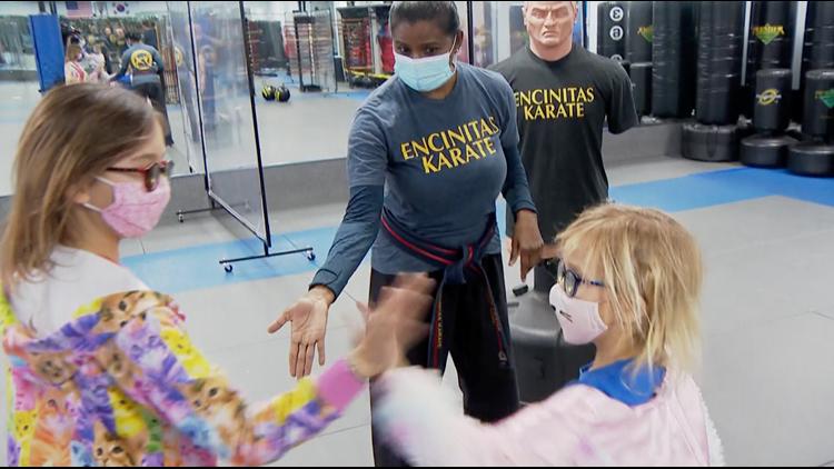 Karate Kindness: Two girls hand a struggling Karate Master $500